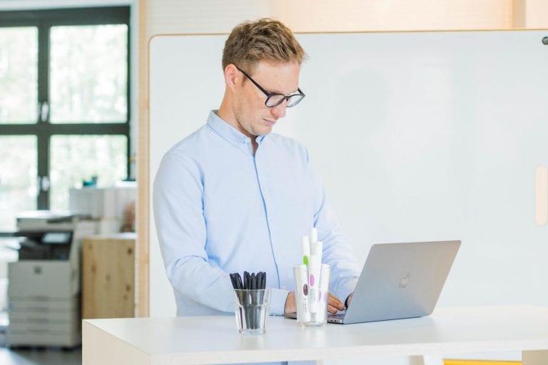 Mann vor Whiteboard an apple MacBook