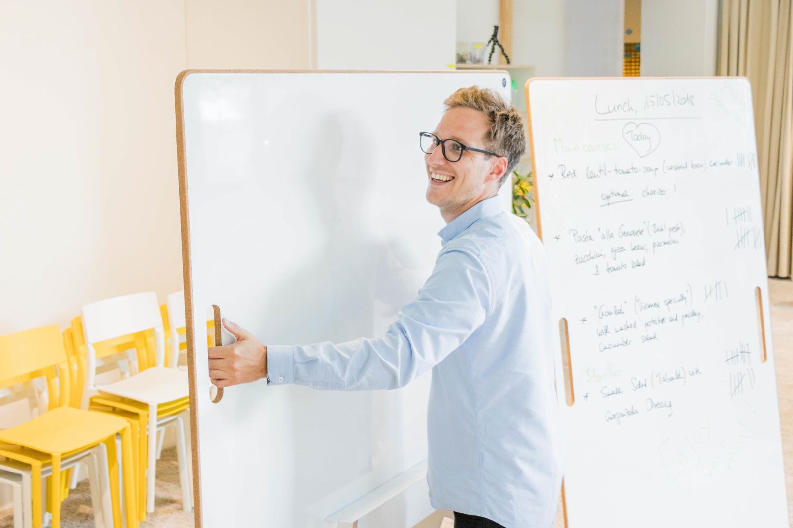 Der lachende Steffen Szary trägt ein agiles Design-Whiteboard