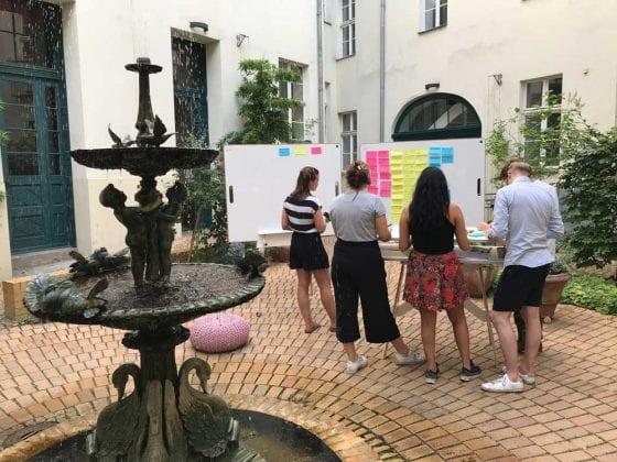 Ein Team beim agilen Arbeiten draußen im Innenhof