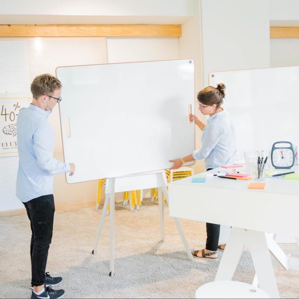 Zwei Menschen in einer Workshopsituation verschieben ein Whiteboard im rollbaren Gestell