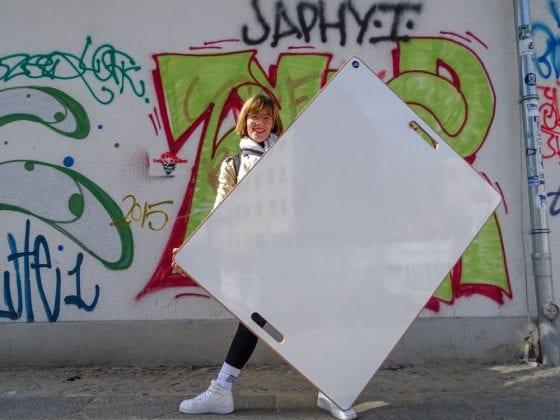 WildBoard von space3000 wird von einer Frau gehalten, vor einer Graffiti Wand in Berlin