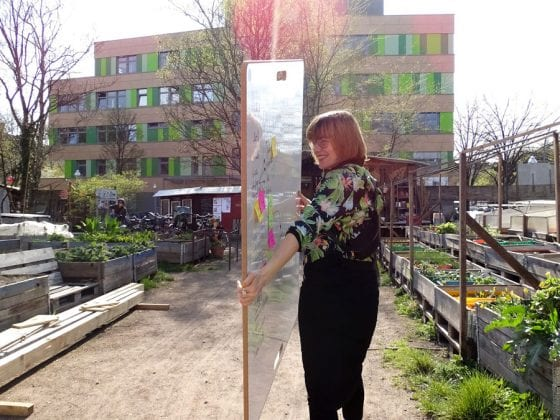 WildBoard Design-Whiteboard wird von einer Frau im himmelbeet Gemeinschaftsgarten getragen