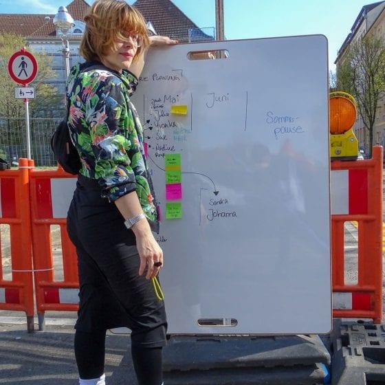 Design-Whiteboard im Berliner Wedding auf einer Straße mit einer Frau davor