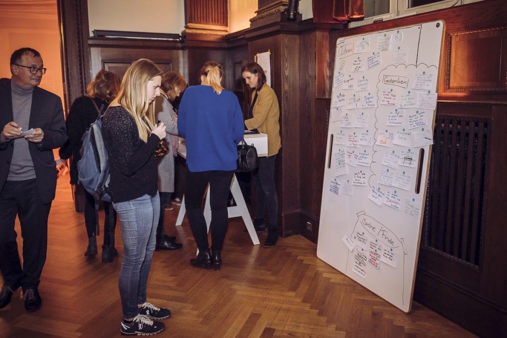 Menschen gucken sich Noitzen auf einem Whiteboard an Foto by Julia Schoierer
