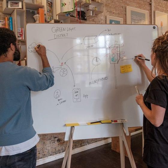Zwei Personen arbeiten an einem Design Whiteboard
