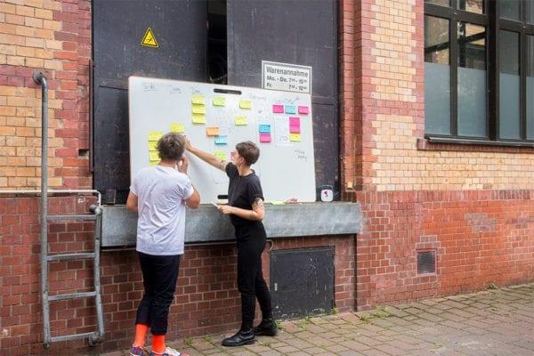 Zwei Personen arbeiten an einem mobilen Design Whiteboard