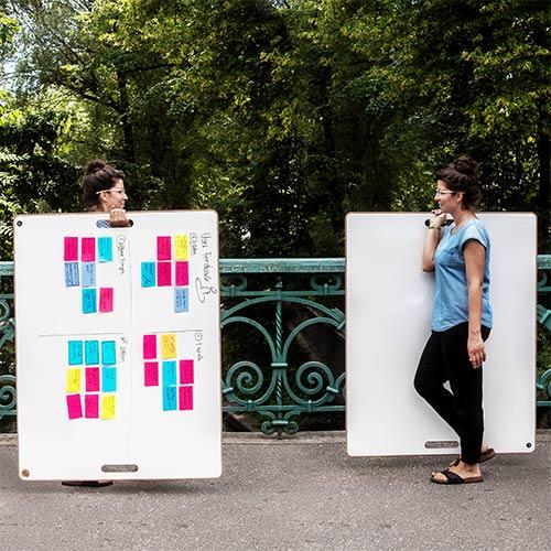 Eine Frau ist zweimal dargestellt. Sie schaut sich selbst an und hält ein Whiteboard in der Hand.