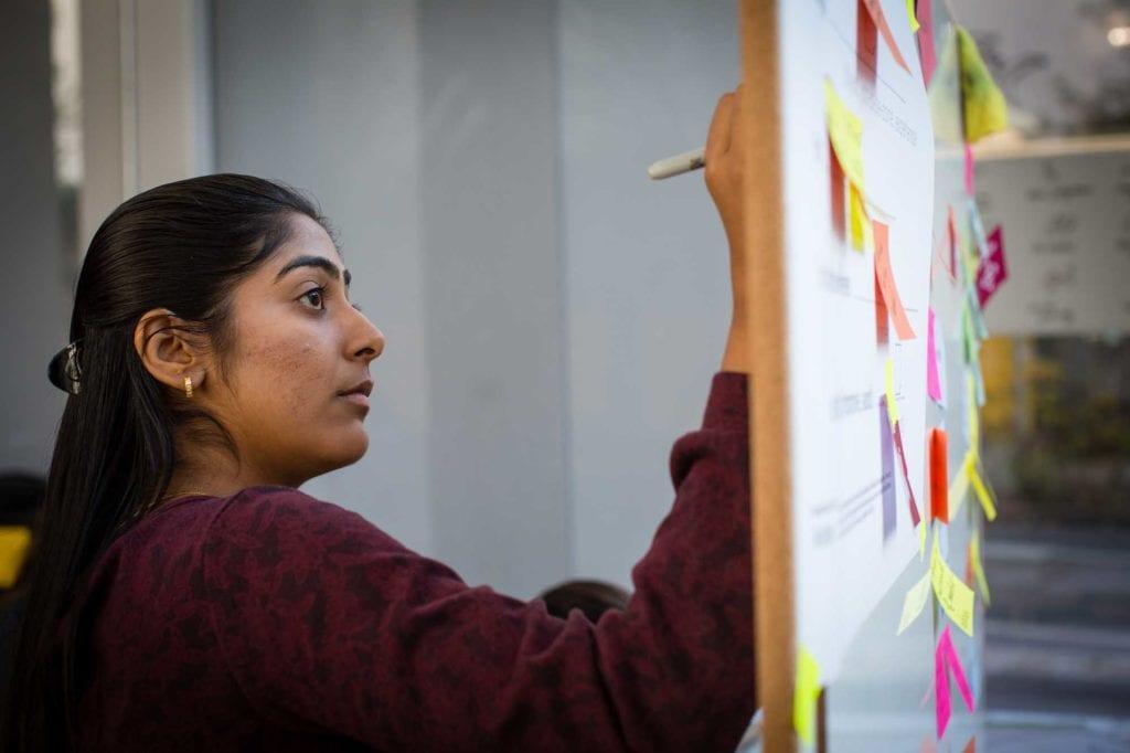 Teilnehmerin an einem Whiteboard mit Post-its