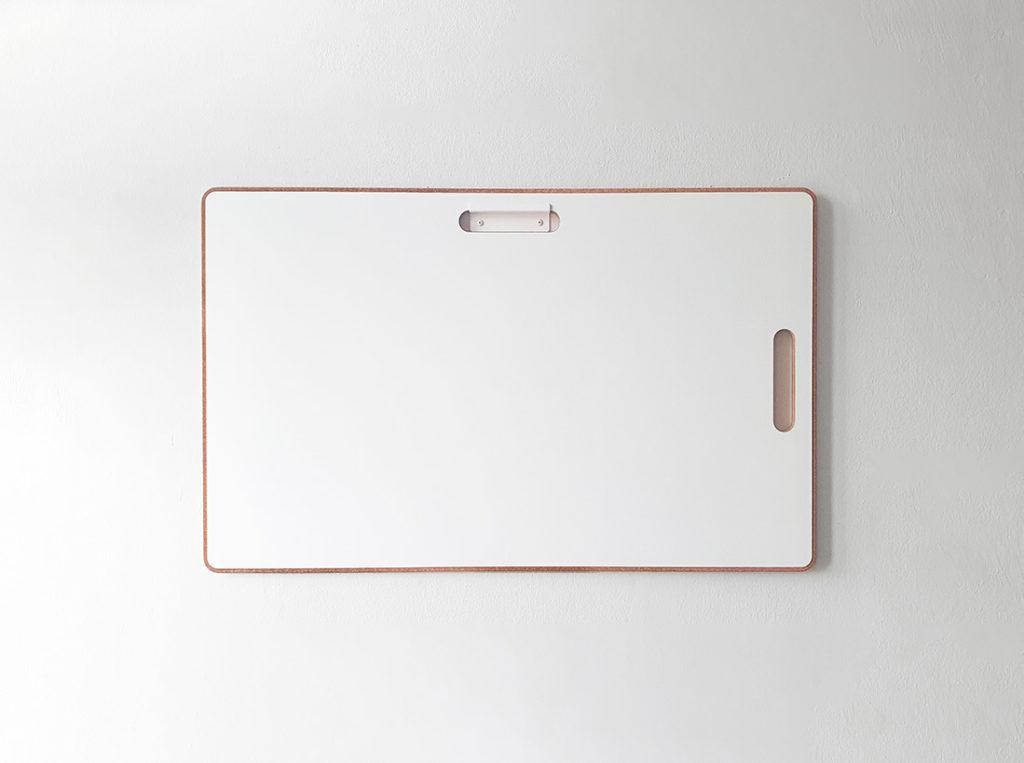 Kleines Design Whiteboard mit Korkrand hängt an einer Wand